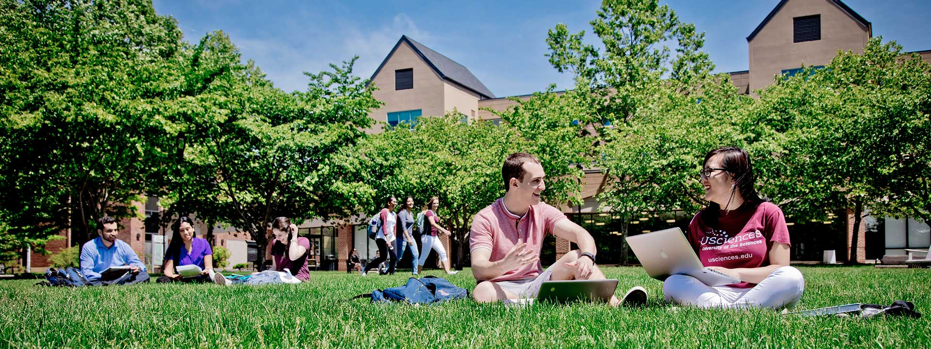 Students sitting on the grassy campus quad