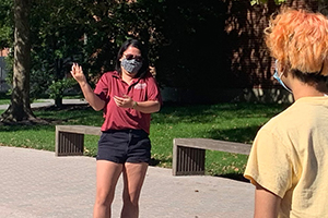 A tour leader wearing a mask guiding a tour group at USciences' campus