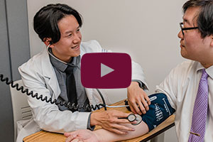 student taking blood pressure - play video button